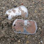 Rusty Steel Dog Tag with random rust spotting in sand